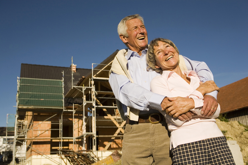 Senior couple embracing in front of construction site, laughing, low angle view